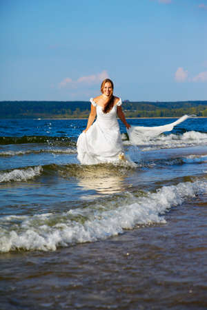 beautiful slavonic bride running in sea waves with bridal in her hands Stock Photo - 9390994