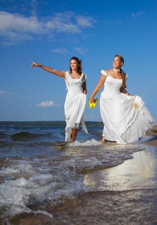 two beautiful slavonic brides walking along coastal strip photo