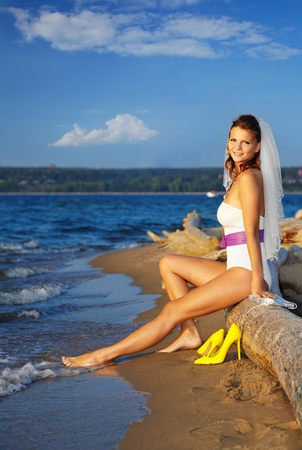 beautiful slavonic bride in body and sun-glasses sitting on trunk. blue sky and sea on backround. photo