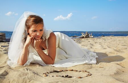 beautiful dreamy slavonic bride laying on sand with heart layed from stones photo