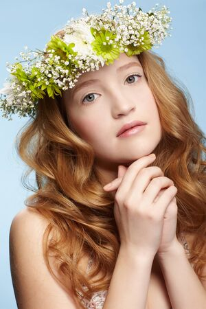 portrait of beautiful healthy redhead teen girl in garland on blue Stock Photo - 9418318