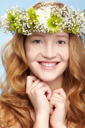 expression portrait of beautiful healthy smiling redhead teen girl in garland on blue photo