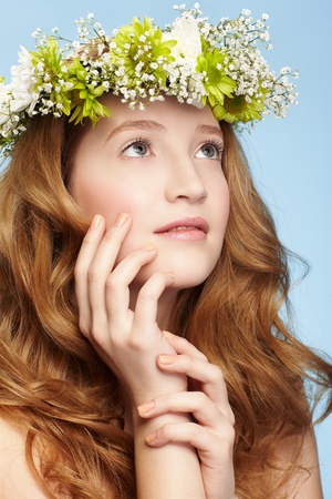portrait of beautiful healthy redhead teen girl in garland on blue photo
