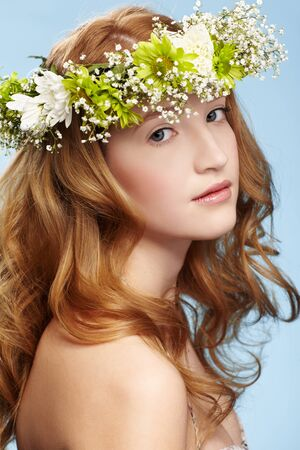 portrait of beautiful healthy redhead teen girl in garland on blue photo