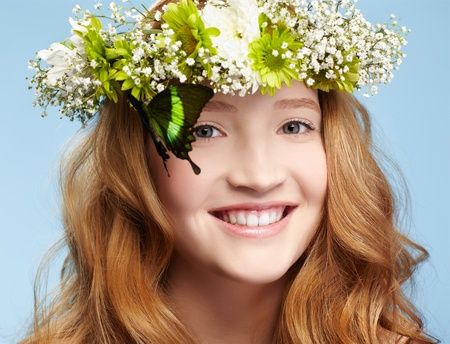 portrait of beautiful healthy redhead teen girl with butterfly sitting on her garland on blue photo