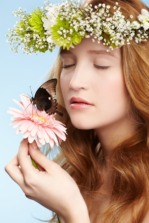 portrait of beautiful healthy redhead teen girl in garland with butterfly on gerbera flower on blue photo