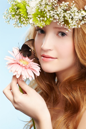 portrait of beautiful healthy redhead teen girl in garland with butterfly on gerbera flower on blue Stock Photo - 9418308