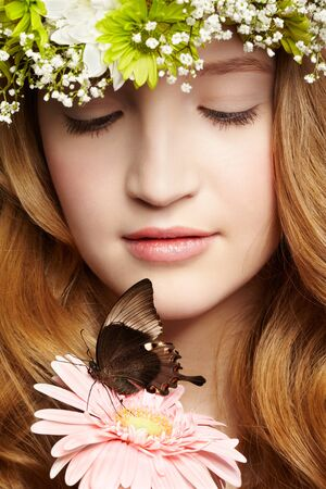 closeup portrait of beautiful healthy redhead teen girl with butterfly on gerbera flower photo