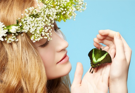 portrait of beautiful healthy redhead teen girl in garland with butterfly on hand on blue photo