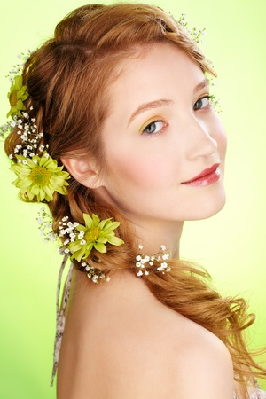 portrait of beautiful healthy redhead teen girl with flowers in her hair on green photo