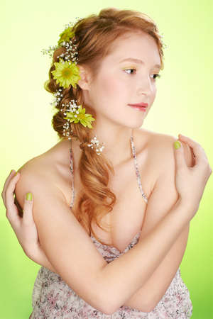 portrait of beautiful healthy redhead teen girl with flowers in her hair on green Stock Photo - 9418292