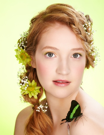 portrait of beautiful healthy redhead teen girl with flowers in her hair holding butterfly on her shoulder photo