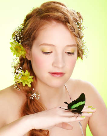 portrait of beautiful healthy redhead teen girl with flowers in her hair holding butterfly on hand photo