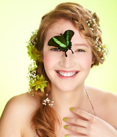 expression portrait of beautiful healthy smiling redhead teen girl with flowers in her hair holding butterfly on her face photo