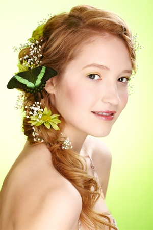 portrait of beautiful healthy redhead teen girl with flowers and butterfly on her hair photo