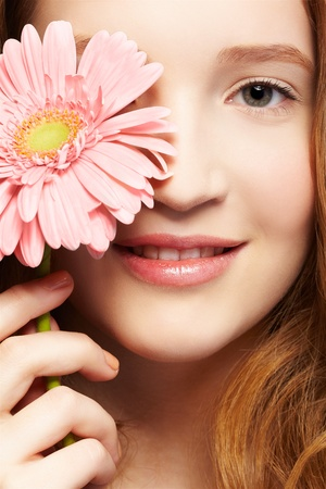 expression closeup portrait of beautiful healthy smiling redhead teen girl with gerbera flower photo