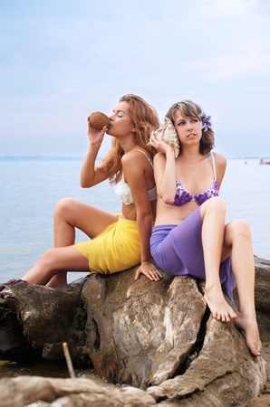 Girls with coconut and shell on the beach photo