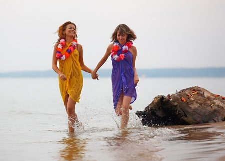 Young girls with flowers running in the water photo