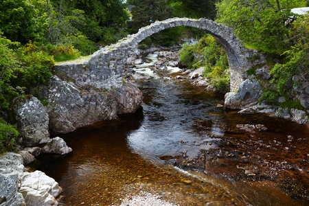 Old stone Packhorse Bridge over the river Dulnain in Carrbridge, Scotland