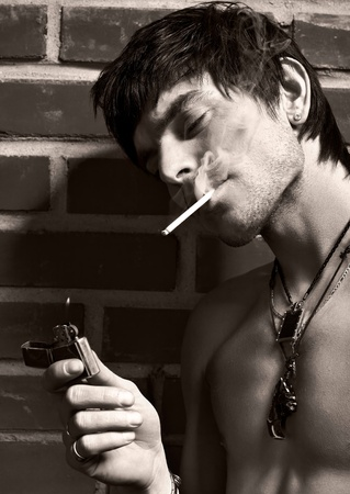 steadfast: Portrait of young  smoking man  posing near brick wall