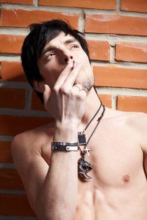 Portrait of young  smoking man  posing near brick wall photo