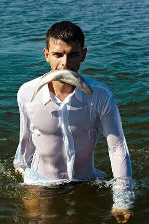 sea fishing: man in classic white shirt walking in water bearing fish in his mouth like a predator Stock Photo