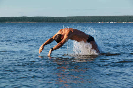 man swimmer comes up from water to dive in it. photo