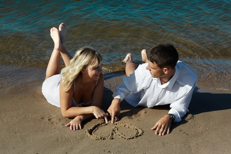romantic slavonic couple  taking their time on the beach - blonde girl in peignoir and brown haired man in white shirt drawing heart on the sand Stock Photo - 9598592