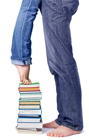 newly married couple: body part portrait of woman and mens legs in jeans. man is standing on floor, girl is standing on the stack of books on tiptoe