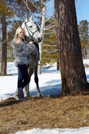 horse blonde: Young blond beautiful woman with light gray horse  Stock Photo