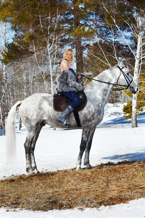 outdoor portrait of beautiful blonde girl in furs with pale horse in sunny winter forest photo