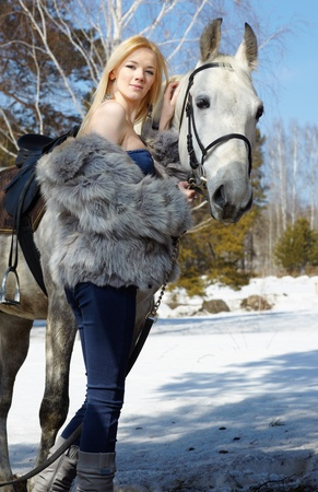 blue grey coat: Young blond beautiful woman with light gray horse  Stock Photo