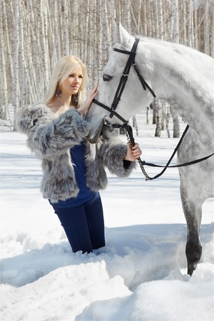 outdoor portrait of beautiful blonde girl with pale horse in sunny winter forest photo