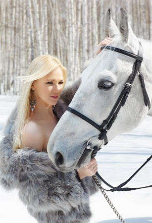 horse blonde: outdoor portrait of beautiful blonde girl with pale horse in sunny winter forest