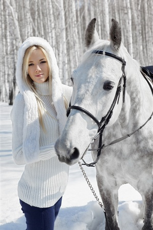 outdoor portrait of beautiful blonde girl with pale horse in sunny winter forest Stock Photo - 9599429