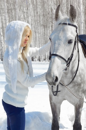 outdoor portrait of beautiful blonde girl with pale horse in sunny winter forest Stock Photo - 9599438