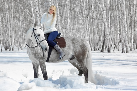 horse blonde: outdoor portrait of beautiful blonde girl sitting on pale horse in sunny winter forest