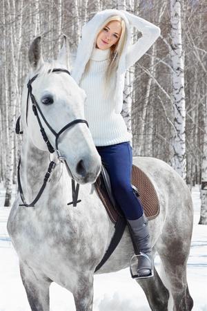 merrie: buiten portret van prachtige blond meisje, zittend op het vale paard in zonnige winter forest Stockfoto