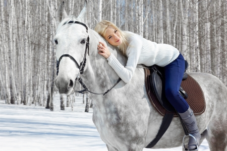 outdoor portrait of beautiful blonde girl sitting on pale horse in sunny winter forest photo