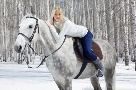 horseback: outdoor portrait of beautiful blonde girl sitting on pale horse in sunny winter forest