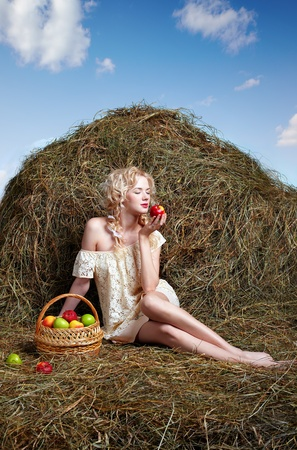 portrait of beautiful blonde country girl posing on yellow hay with basket of apples photo