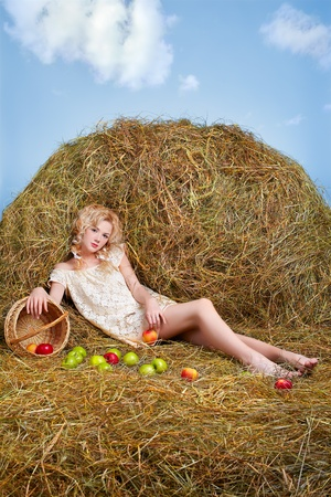 portrait of beautiful blonde country girl posing sitting on yellow hay with apples spilled from basket photo