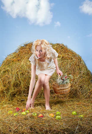 portrait of beautiful blonde country girl posing on yellow hay with basket gathering spilled apples photo