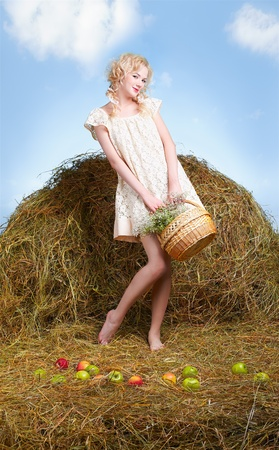 portrait of beautiful blonde country girl posing on yellow hay with basket of apples Stock Photo - 9599742