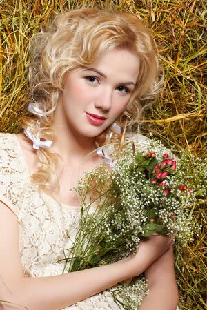 portrait of beautiful blonde country girl sittitng on yellow hay with bunch of flowers photo