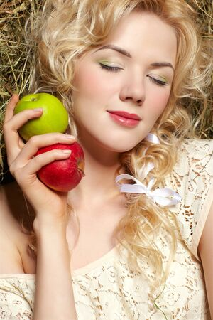 portrait of beautiful blonde country girl sittitng on yellow hay with apples photo