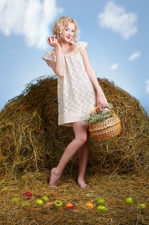 portrait of beautiful blonde country girl sittitng on yellow hay photo