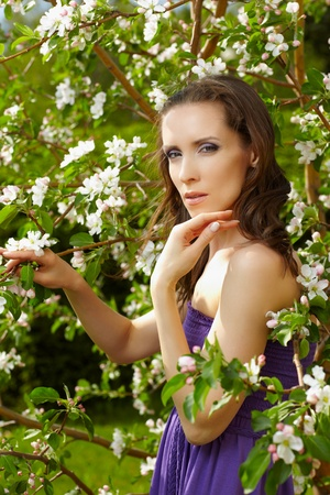 outdoor portrait of beautiful woman with fresh skin posing near blooming apple tree Stock Photo - 9782206