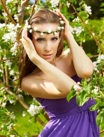 outdoor portrait of beautiful woman with fresh skin posing in garland near blooming apple tree Stock Photo - 9782180