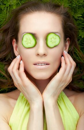 outdoor portrait of beautiful woman laying on green grass with slices of cucumber on eyes photo